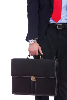Man in suit carrying suit case in hand