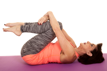 Woman laying down and stretching her buttock and lower back by bringing her knees up to her chest