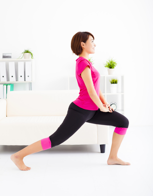 Woman in pink performing the lunch stretch for the hip flexor muscle